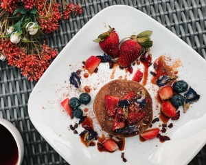 Pancakes covered in blueberries and strawberries on a white plate, next to autumnal flowers and a cup of black coffee